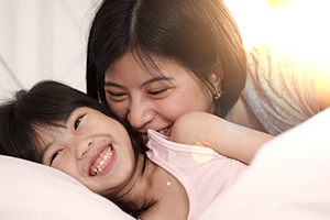 Mother and daughter with comfortable bedding